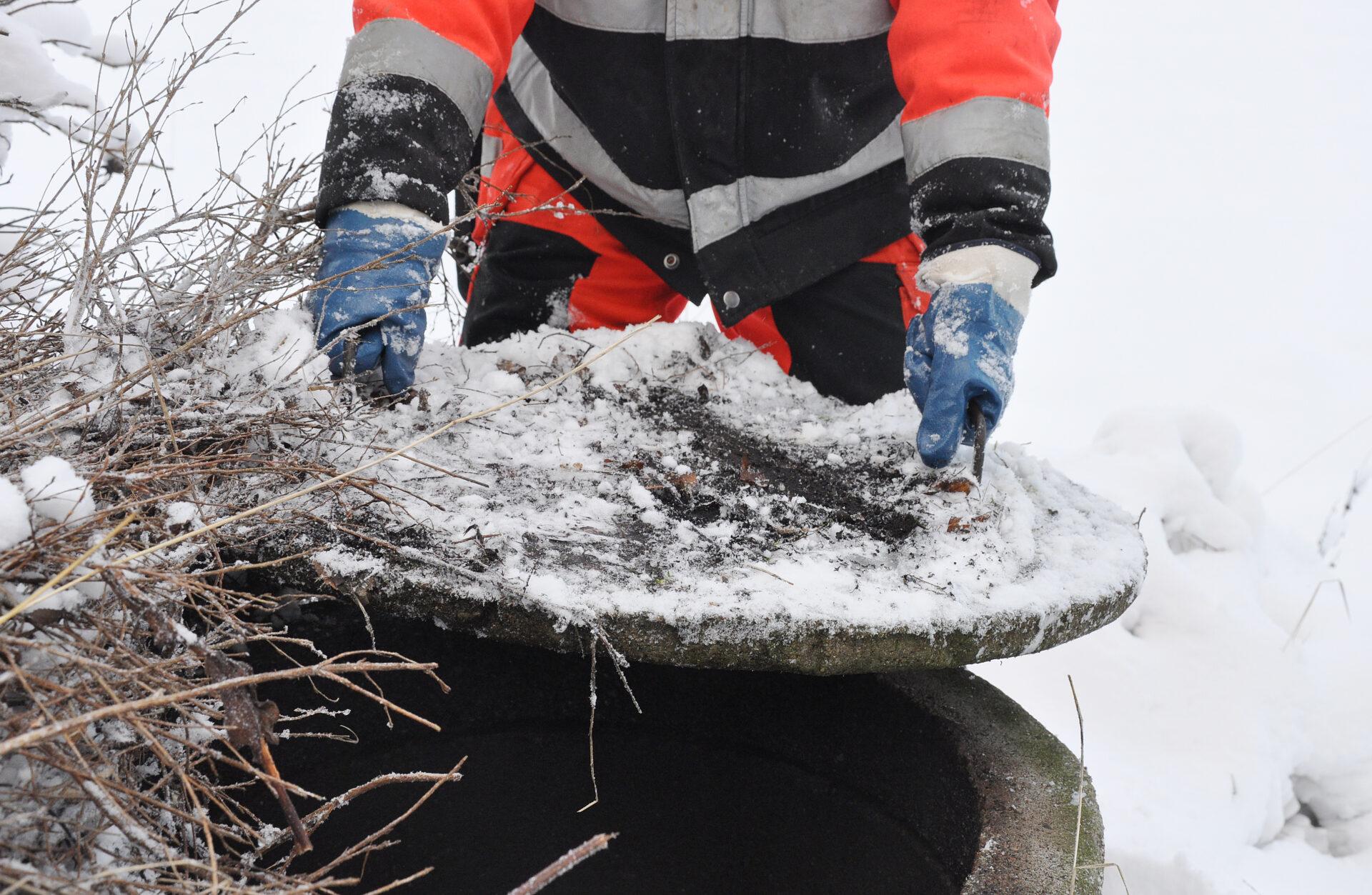 Person lyfter brunnslock för att rensa avlopp från rötter och beläggningar.